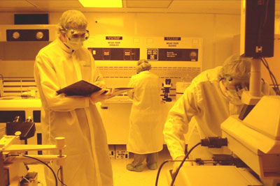 Graduate and undergraduate students work together processing devices inside the clean room.