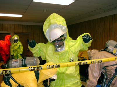 A decon team in Level B suits are decontaminating a member of Entry Team 1 after they have left the Hot Zone.