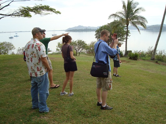 (From left,) Steve Bellinger, tour guide Stan McRay, a tourist, Mark Harrison and Walter McNeil look over a bay on O'ahu.