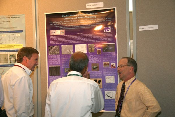 Prof. McGregor discussing the details of his poster regarding compact wireless modules for neutron detection and gamma ray spectroscopy.