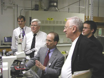 Mike Whaley, Dr. Shultis, Dr. Foulkes, and Troy Unruh look on as Dr. McGregor demonstrates an infrared microscope.
