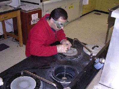 Alireza Kargar grinds CdZnTe samples to remove saw damage, and to shape the pieces for lapping and polishing.