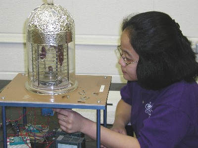 Elsa Ariesanti makes fine adjustments to the HgI2 vertical furnace temperature. Shown on the furnace pedestal is a sizable HgI2 single crystal.